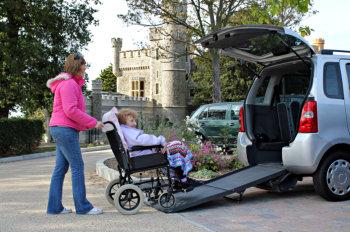 woman assisting elderly woman in wheelchair